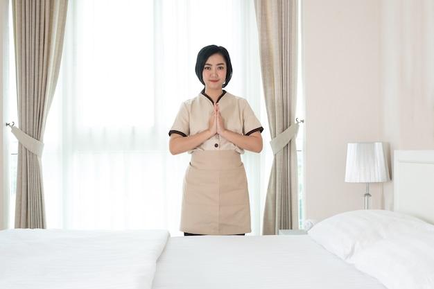La giovane cameriera asiatica alza una mano per rendere omaggio nella stanza d'albergo