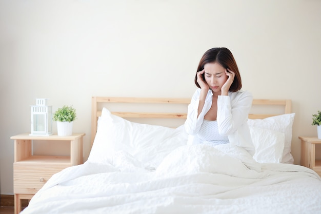 La giovane camicia bianca d'uso della donna asiatica attraente e sexy ha ottenuto l'emicrania sul letto in camera da letto bianca con il fronte infelice.
