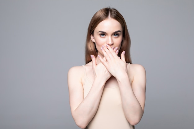 La giovane copertura graziosa della donna con le mani la sua bocca ha sorpreso isolata sulla parete bianca