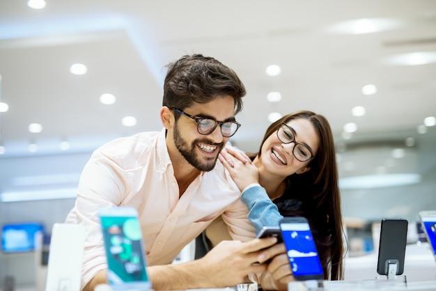 La giovane coppia affascinante ed elegante soddisfatta ha abbracciato testando il nuovo modello di cellulare dalla scrivania nel negozio di tecnologia.