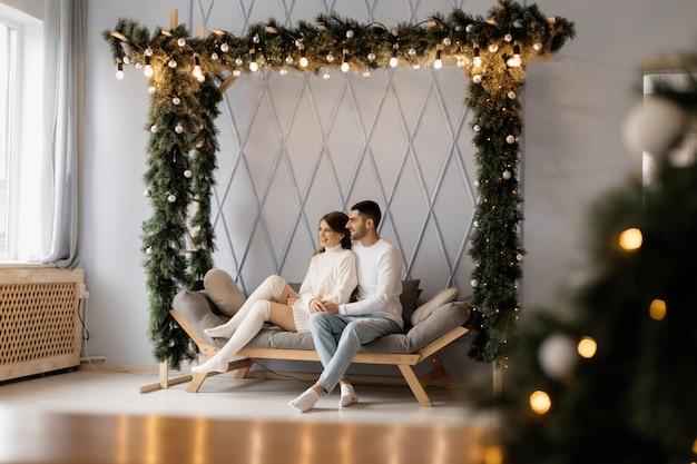 La giovane coppia affascinante in vestiti domestici bianchi accoglienti posa in una stanza con l'albero di natale