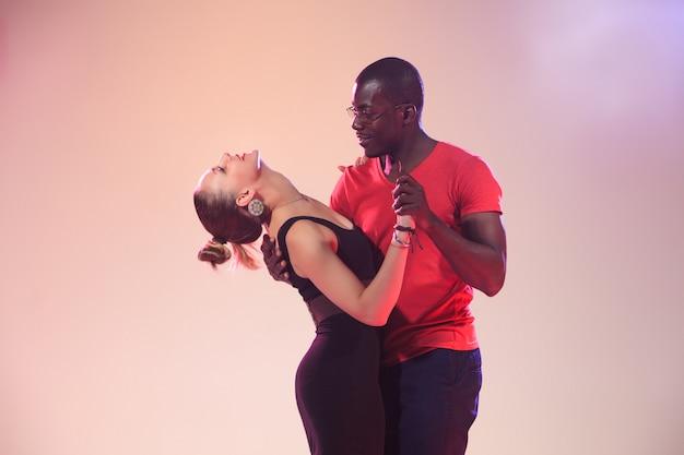 La giovane coppia balla la salsa caraibica sociale