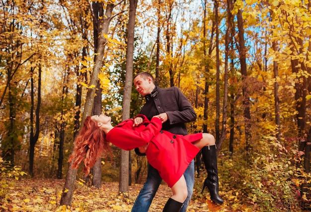La giovane coppia balla nella foresta di autunno fra gli alberi variopinti