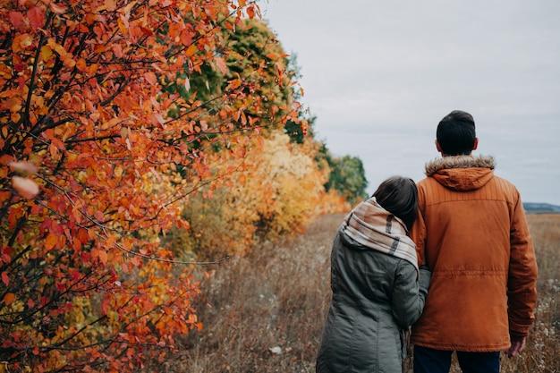 La giovane coppia cammina nella foresta di autunno fra gli alberi variopinti