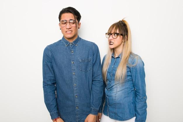 La giovane coppia con gli occhiali è un po 'nervosa e spaventata premendo i denti