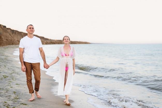 La giovane coppia di sposi cammina lungo la costa del mare.