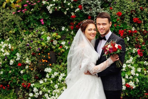 La giovane coppia è in piedi sullo sfondo del giardino fiorito
