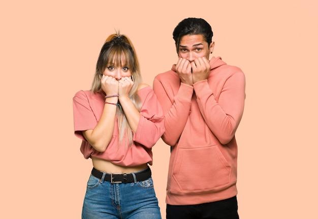 La giovane coppia è un po 'nervosa e spaventata mettendo le mani in bocca