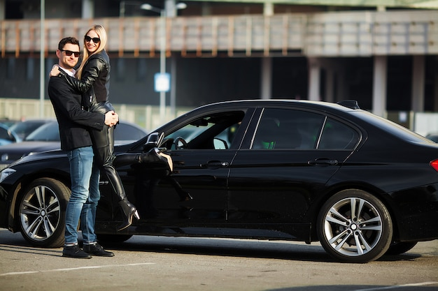 La giovane coppia felice sceglie e acquista una nuova auto per la famiglia
