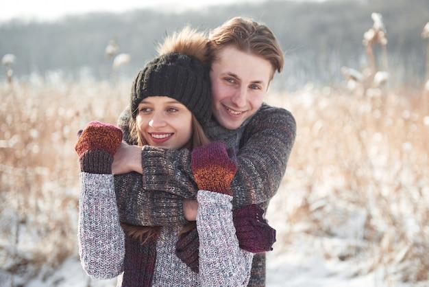 La giovane coppia felice si diverte su neve fresca alla bella giornata di sole invernale in vacanza
