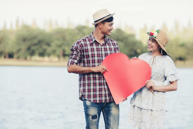La giovane coppia felice sta tenendo i cuori di carta rossi