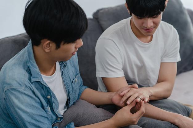 La giovane coppia gay asiatica propone a casa, gli uomini sorridenti coreani adolescenti lgbtq sorridono felici mentre propongono e la sorpresa del matrimonio indossa l'anello nuziale nel salotto di casa.