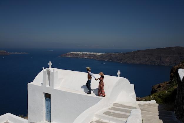 La giovane coppia guarda dall'alto in basso il paesaggio dell'isola di santorini