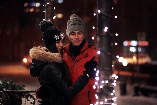 La giovane coppia in maglioni e berretti abbraccia sulla via dell'inverno. in amore in una ghirlanda.