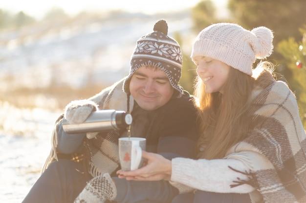 La giovane coppia innamorata beve una bevanda calda da un thermos, seduto in inverno nella foresta, nascosto in tappeti caldi e confortevoli e godersi la natura