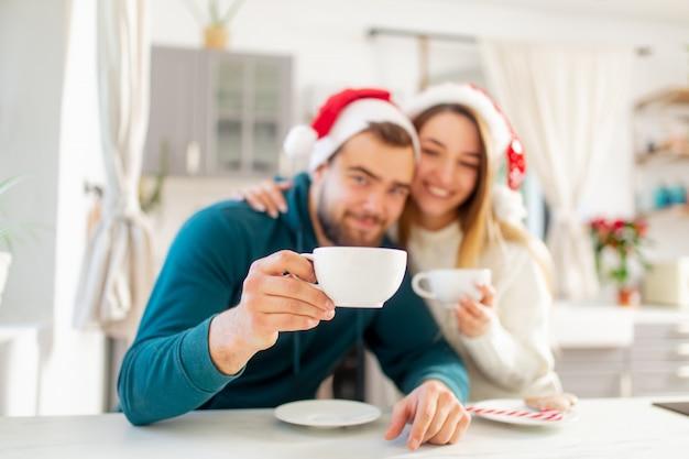 La giovane coppia sposata in cappelli di natale beve il caffè nella cucina