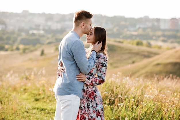 La giovane coppia sta abbracciando e camminando nel campo estivo con erba sulla città di sfondo. uomo e donna. concetto di famiglia adorabile.