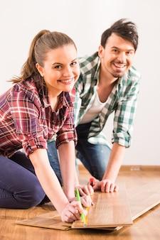 La giovane coppia sta installando il pavimento laminato nella stanza.