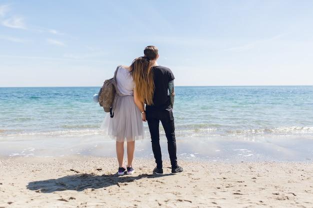 La giovane coppia sta levandosi in piedi vicino al mare