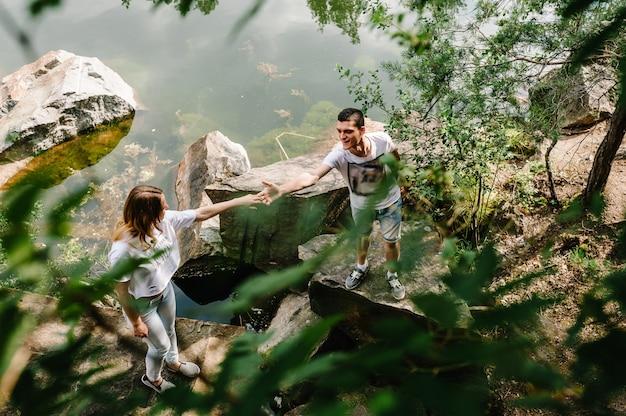 La giovane coppia sta sulla pietra vicino al lago