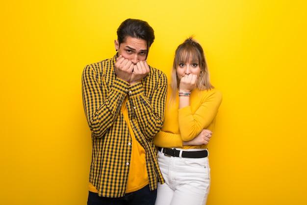 La giovane coppia su uno sfondo giallo vivace è un po 'nervosa e spaventata