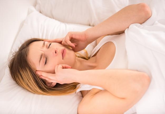 La giovane donna a letto a casa ha mal di testa.