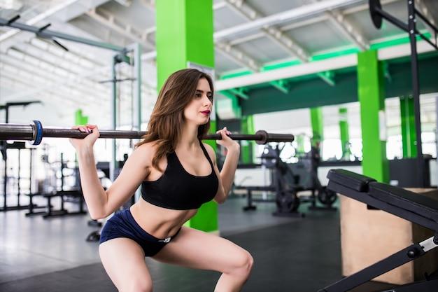 La giovane donna abbastanza allegra che fa gli esercizi che accovaccia con il bilanciere si è vestita in abiti sportivi di modo in sportclub