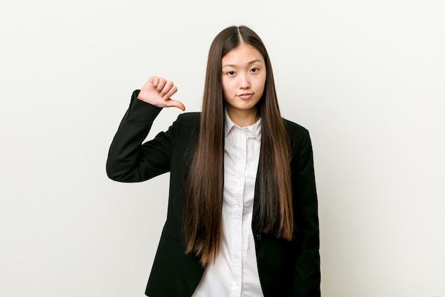 La giovane donna abbastanza cinese di affari che mostra un gesto di avversione, sfoglia giù.