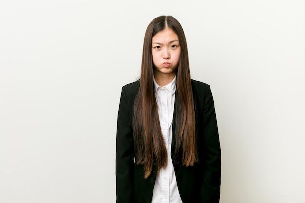 La giovane donna abbastanza cinese di affari soffia le guance, ha espressione stanca. concetto di espressione facciale.