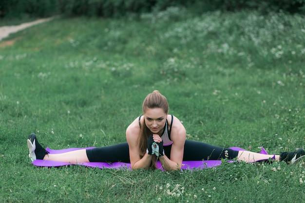 La giovane donna adatta nell'abbigliamento sportivo esegue lo stretching dopo un allenamento fuori