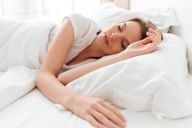 La giovane donna addormentata si trova a letto con gli occhi chiusi.