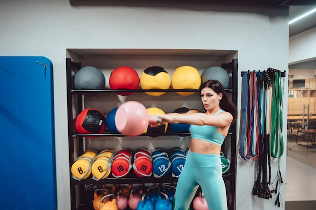 La giovane donna adulta che fa la forza si esercita in ginnastica