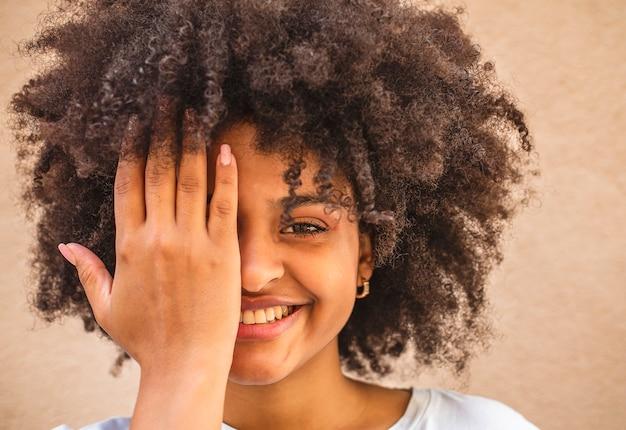 La giovane donna africana dà una occhiata con la sua mano che esamina la parte anteriore