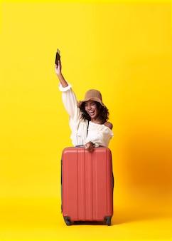 La giovane donna africana si è vestita in vestiti dell'estate che tengono il passaporto con la valigia sopra fondo giallo