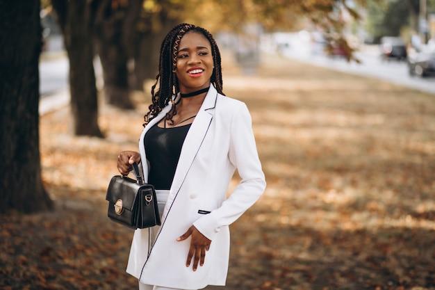 La giovane donna africana si è vestita in vestito bianco in parco