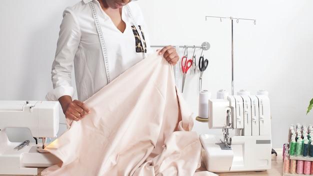 La giovane donna africana sta cucendo abiti moderni nella sua officina