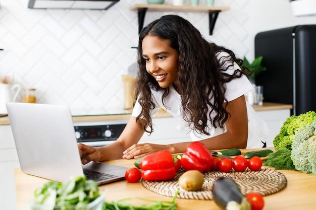 La giovane donna africana sta scrivendo qualcosa in un computer portatile su uno scrittorio della cucina con le verdure