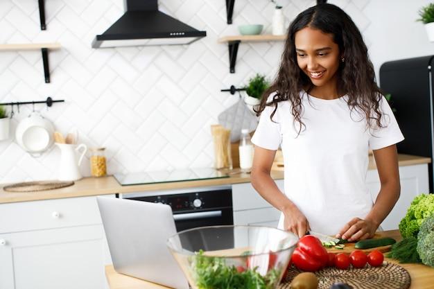 La giovane donna africana sta tagliando un cetriolo e guarda in un computer portatile