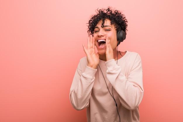 La giovane donna afroamericana che ascolta la musica che grida ha eccitato alla parte anteriore