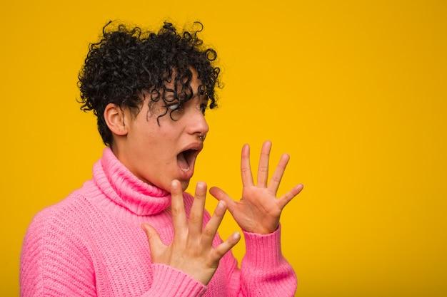 La giovane donna afroamericana che indossa un maglione rosa grida forte, tiene gli occhi aperti e le mani tese.