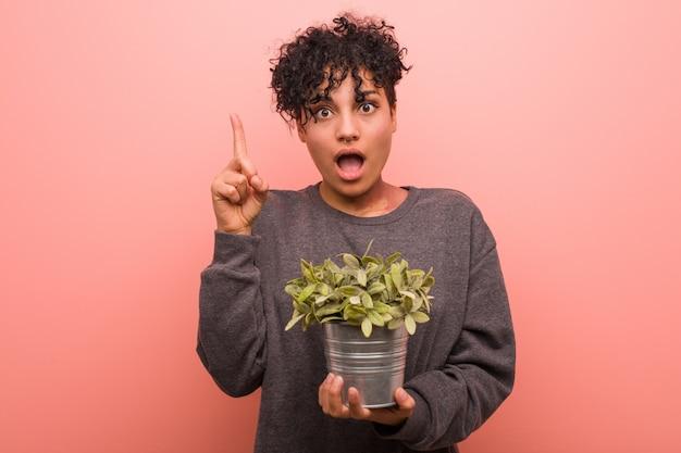La giovane donna afroamericana che tiene una pianta si è distesa pensando a qualcosa alla a.