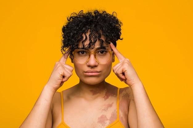 La giovane donna afroamericana con il segno di nascita della pelle si è concentrata su un compito, mantenendo l'indice che punta la testa