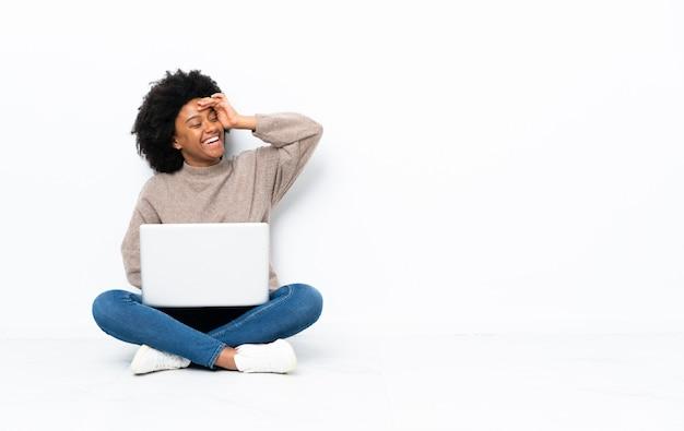 La giovane donna afroamericana con un laptop seduto sul pavimento ha realizzato qualcosa e intendendo la soluzione