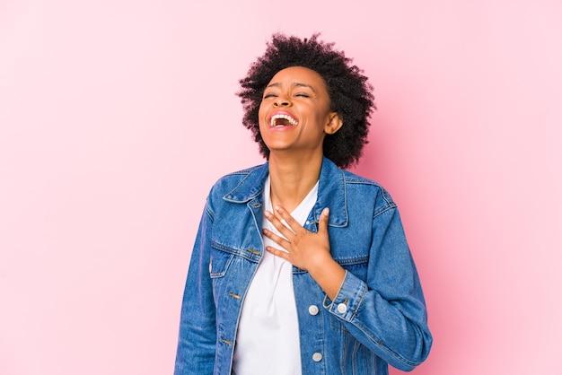 La giovane donna afroamericana contro un backgroound rosa isolato ride ad alta voce mantenendo la mano sul petto.