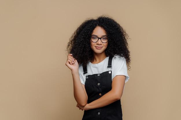 La giovane donna afroamericana dall'aspetto piacevole tocca i capelli ricci, ha un'acconciatura folta, indossa occhiali da vista