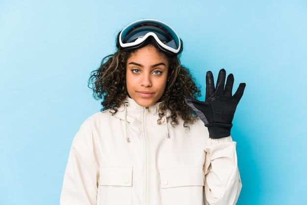La giovane donna afroamericana dello sciatore ha isolato sorridente allegro che mostra il numero cinque con le dita.