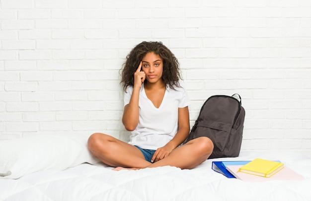 La giovane donna afroamericana dello studente sul letto che indica il tempio con il dito, pensando, si è concentrata su un compito.