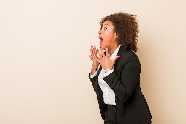 La giovane donna afroamericana di affari grida forte, tiene gli occhi aperti e le mani tese.