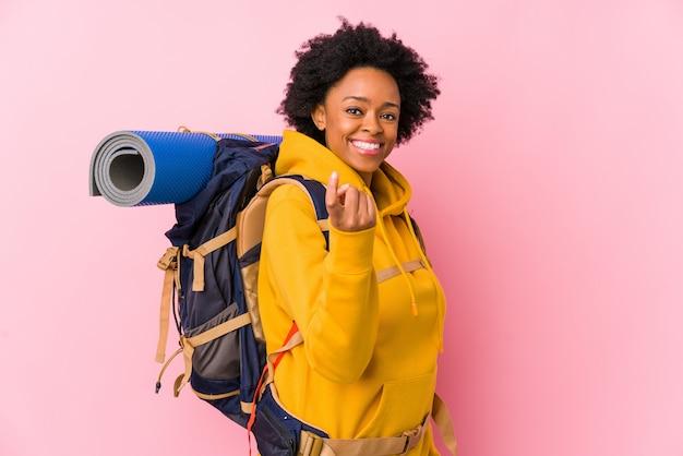 La giovane donna afroamericana di viaggiatore con zaino e sacco a pelo ha isolato indicare con il dito voi come se l'invito si avvicini.