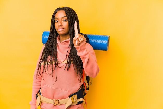 La giovane donna afroamericana di viaggiatore con zaino e sacco a pelo ha isolato la mostra del numero uno con il dito.